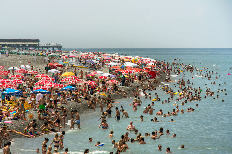 Hoards of sun seekers and beach goers crowd the pebble and black sand and swim in the black sea of Batumi, Georgia. Architecture Beach Crowd Day Group Of People High Angle View Holiday Horizon Horizon Over Water Land Large Group Of People Nature Outdoors Real People Sea Sky Travel Destinations Trip Vacations Water