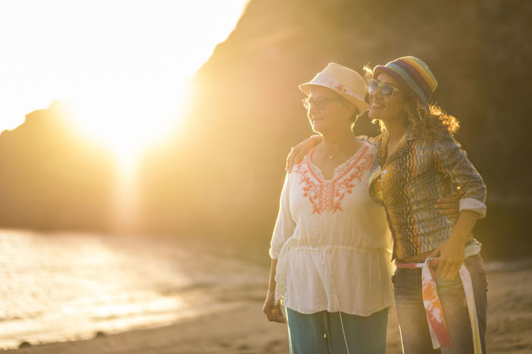 Mother and daughter caucasian people friends at the beach hugging and having fun smiling with golden sun in backlight and ocean in background - family and mixed diversity generations concept Two People Women Togetherness Adult Sunlight Emotion Couple - Relationship Love Sunset Land Back Lit Bonding Sky Nature Positive Emotion Smiling Three Quarter Length Beach Lens Flare Outdoors Family Mother And Daughter Island Caucasian Hippie