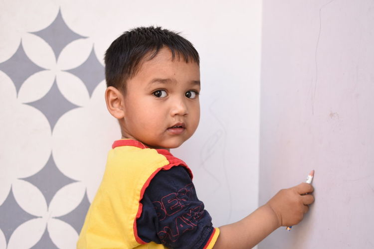 Portrait of boy writing on wall with pencil