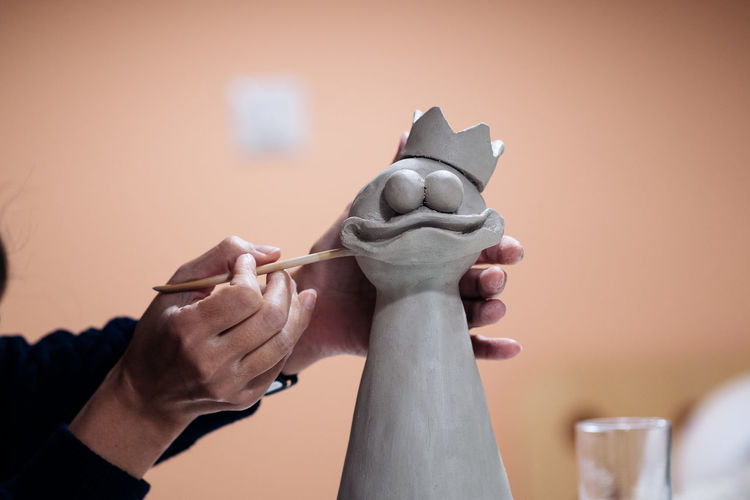 Cropped Image Of Artist Sculpting Bird At Workshop