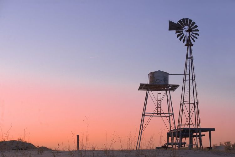 Traditional windmill against sky during sunset