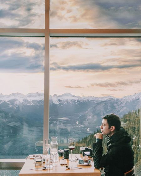 Beauty In Nature Cloud - Sky Coffee - Drink Cold Temperature Day Food And Drink Indoors  Leisure Activity Lifestyles Men Mountain Mountain Range Nature Real People Scenics Sky Snow Table Technology Togetherness Two People Vacations Window Winter Wireless Technology