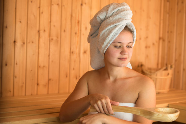 Beautiful Young Woman Holding Wooden Spoon While Sitting In Sauna