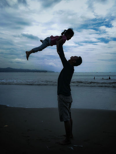 Cheerful Father Lifting Daughter At Beach Against Sky