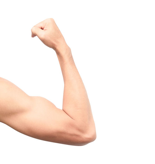 Close-up of man flexing muscles against white background