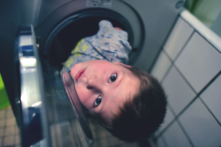 High Angle Portrait Of Boy In Washing Machine