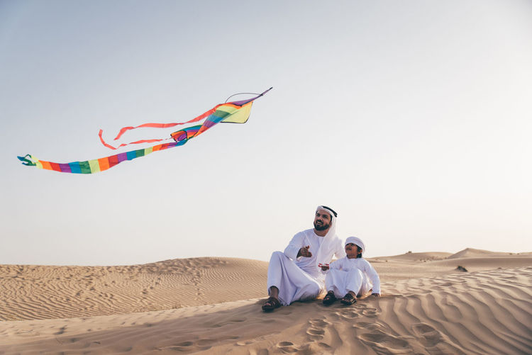 People sitting on desert against clear sky