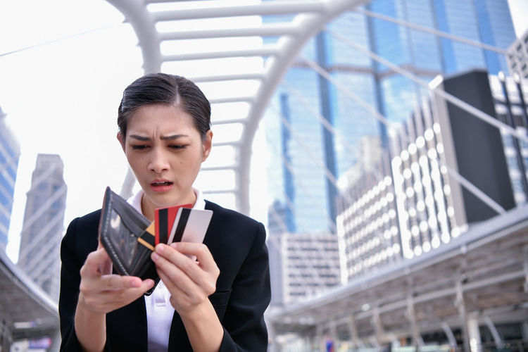 Worried Businesswoman Looking Credit Cards And Empty Purse