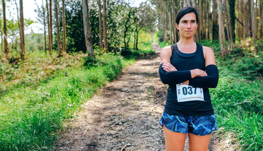 Woman standing with marathon bib in forest
