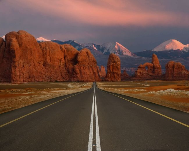 Empty road leading towards rock formations against sky during sunset