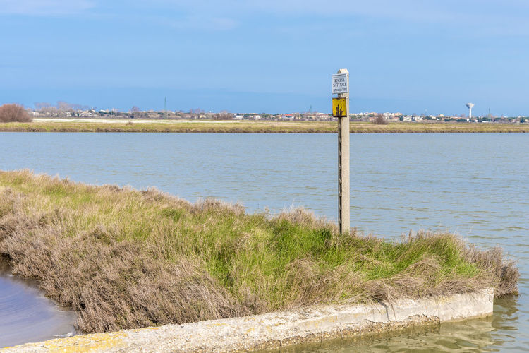 Italy, Cervia. This city is famous for its salt. Saltern date back to ancient times. Beach Beauty In Nature Blue Day Grass Land Nature No People Non-urban Scene Outdoors Plant Pole Scenics - Nature Sea Sky Tranquil Scene Tranquility Water Wooden Post