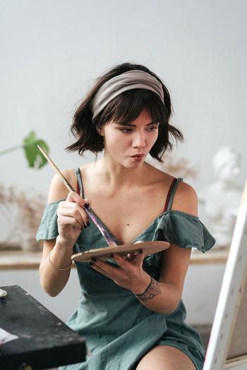 Female painter holding palette and paintbrush at art studio