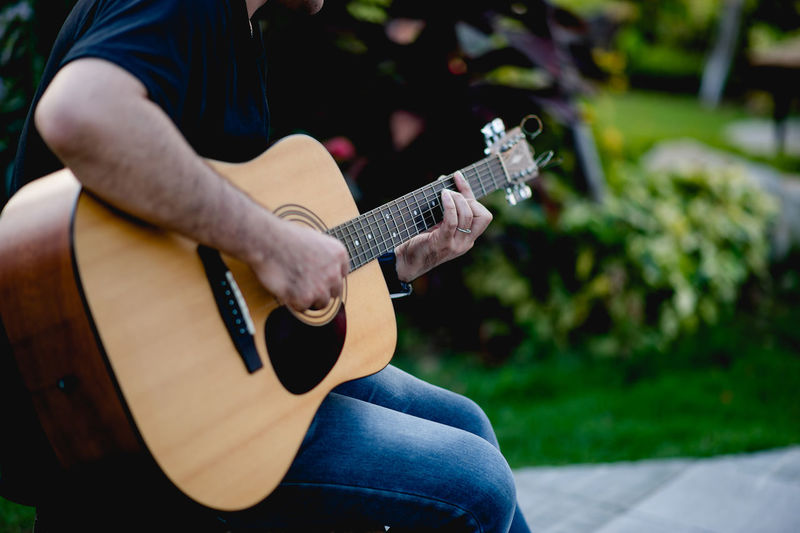 Midsection of man playing guitar outdoors