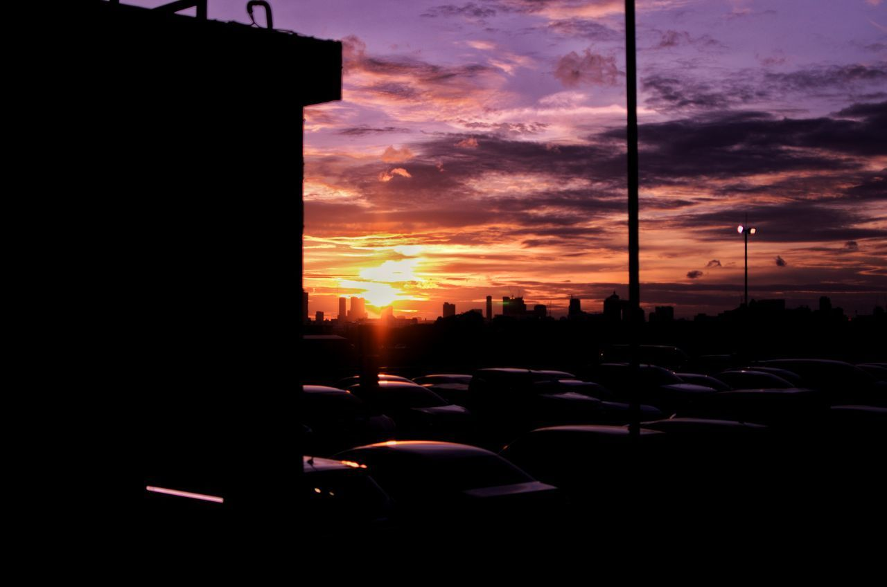 sunset, sky, car, motor vehicle, mode of transportation, transportation, land vehicle, cloud - sky, city, silhouette, architecture, built structure, building exterior, street, no people, orange color, nature, traffic, outdoors, road