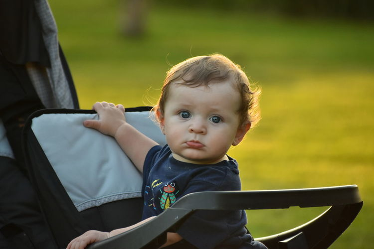 Portrait of cute baby boy in carriage at park