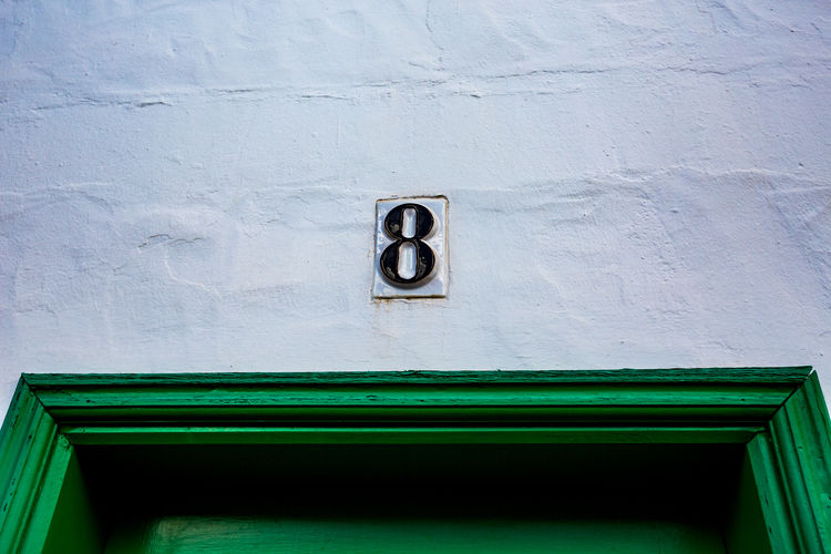 Ceramic black number eight, 8 outside on white painted wall over green wooden door 8 Lanzarote Lanzarote Island Lanzarote-Canarias Number 8 Number Eight Architecture Building Building Exterior Built Structure Close-up Day Door Eight Entrance Green Color House Low Angle View No People Number Numbers Outdoors Textured  Wall - Building Feature White Color