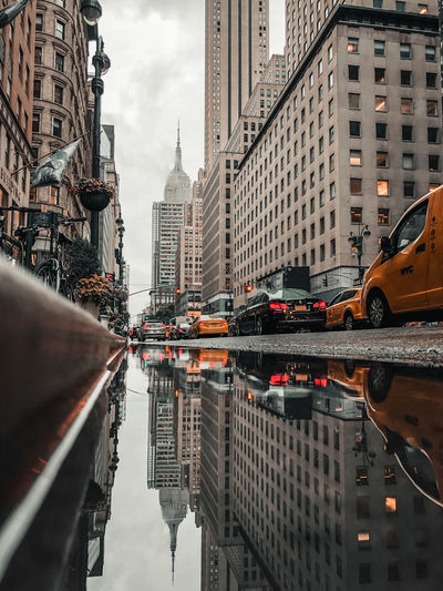 Reflection of buildings on puddle new york city empire state building