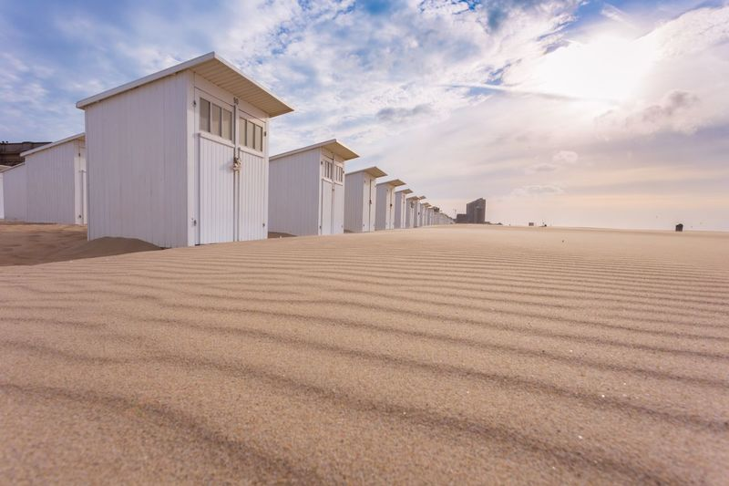 Beach houses on sand against sky