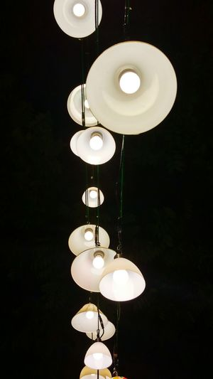 Low Angle View Of Illuminated Pendant Lights Hanging At Night