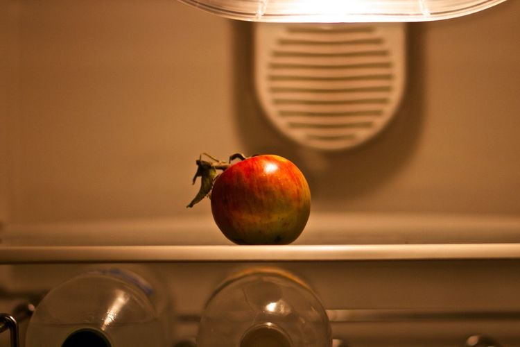 Apple Over Bottles In Illuminated Refrigerator