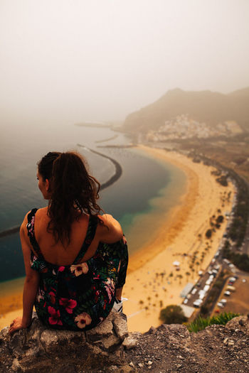 Rear View Of Woman Looking At Sea On Cliff