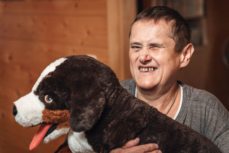Happy woman with mental disability holds her toy stuffed animal dog in her arms