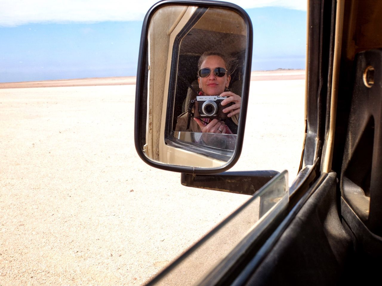 Reflection of woman photographing in side-view mirror of car