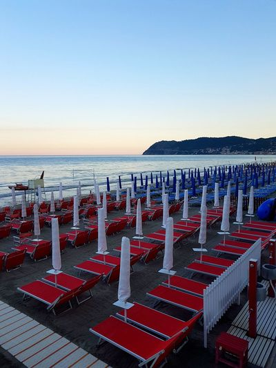 Horizon Over Water Sea In A Row Beach Large Group Of Objects No People Outdoors Red Day Water Clear Sky Sky Nature Travel Destinations Liguria, Italy Tourist Destination Tranquility Sunset Beach