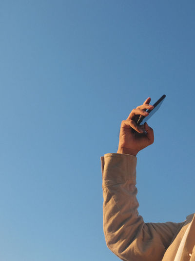 Low angle view of hand holding smart phone against clear sky