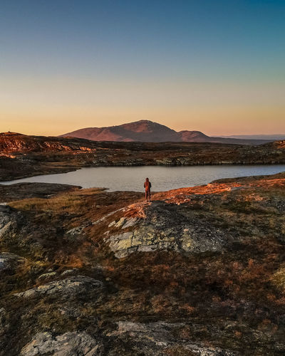 High angel view of man standing on rock against lake and sky during sunset