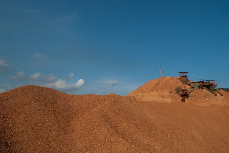 Sand Dunes At Mining Site Against Sky