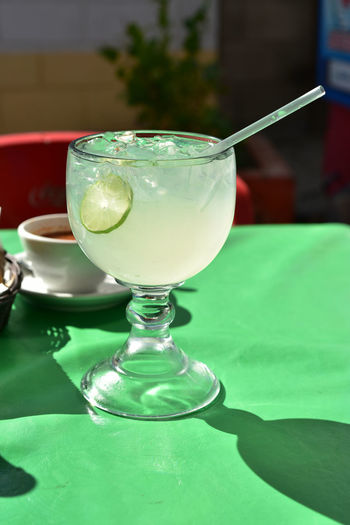 Large glass of lemonade with lime slice in glass and plastic straw, served in mexican restaurant