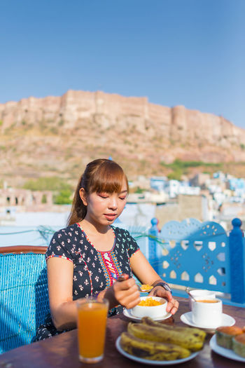 Woman having food while sitting at restaurant against fort