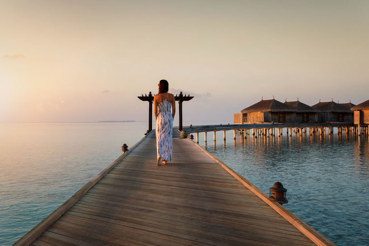 Woman in a dress walking down a wooden jetty during an idyllic sunset in the Maldives Dress Indian Ocean Maldives Tranquility Travel Woman Beauty In Nature Horizon Over Water Hotel Idyllic Island Jetty Leisure Activity Lifestyles One Person Pier Rear View Resort Scenics - Nature Sea Sky Sunset Trip Vacations Water