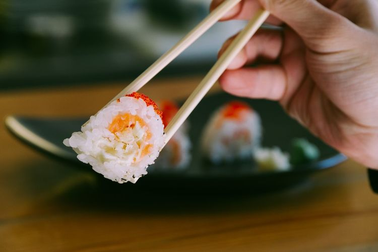 Cropped Hand Of Person Having Sushi With Chopsticks On Table
