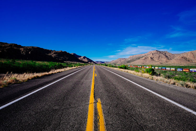 Empty road against blue sky