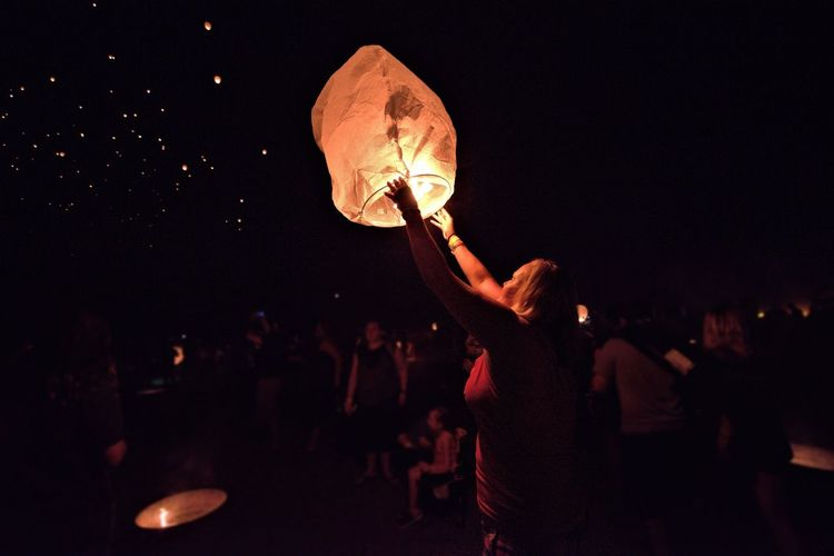 Side view of woman flying illuminated paper lantern in sky at night