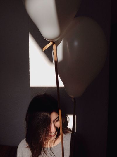 Happy Woman Holding Balloons Against Wall At Home