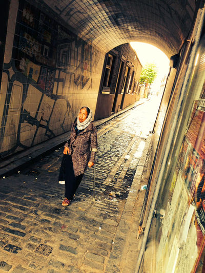 Elderly Asian woman walking through cobbled tunnel Asian Woman Shoreditch Adult Adults Only City City Life Day Elderly Woman Full Length Headscarf Lifestyles One Person One Woman Only Outdoors People Real People Walking Women