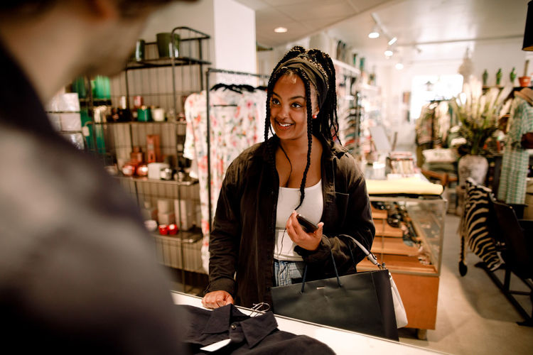 Portrait of smiling woman standing at store