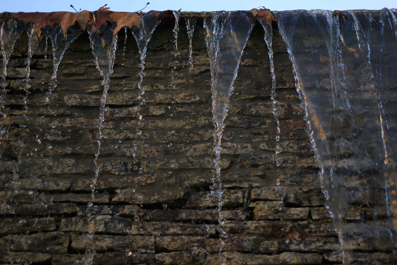 Low Angle View Of Water Flowing From Wall