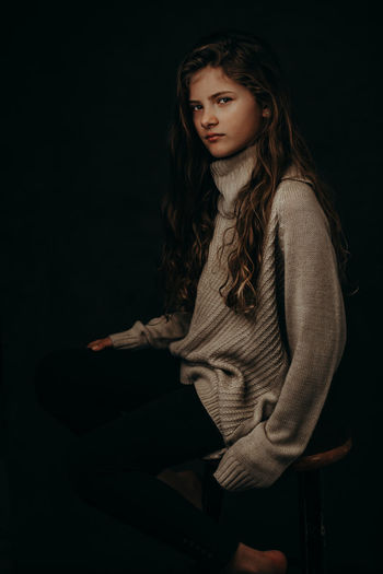 Portrait of cute girl sitting on stool against black background