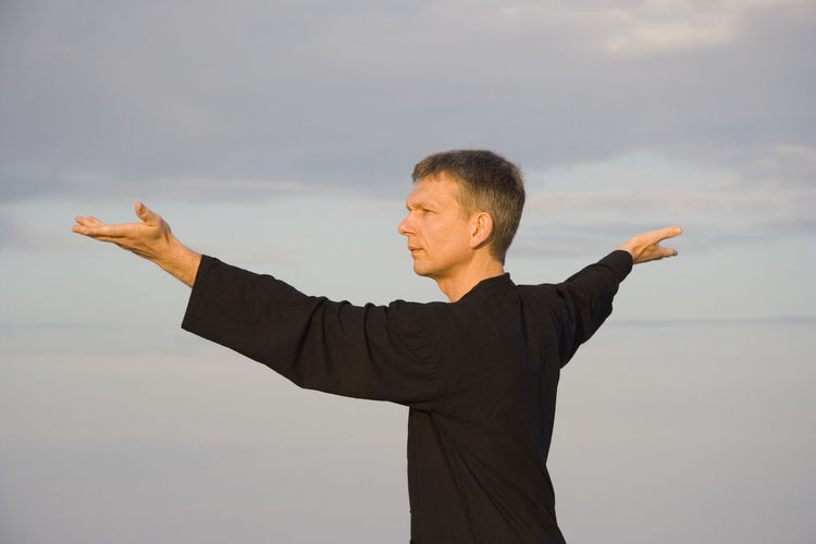 Man practicing tai chi against sky