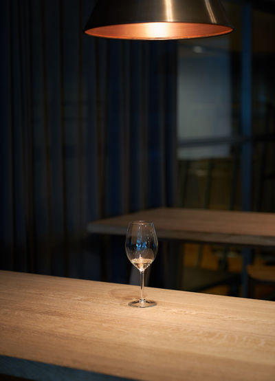 Illuminated lamp with wine glass on table in restaurant