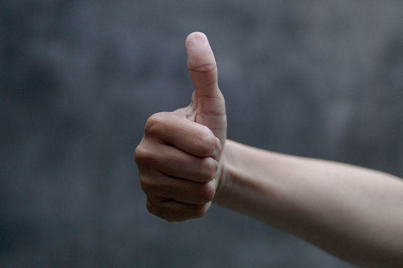 Cropped image of hand gesturing thumb up