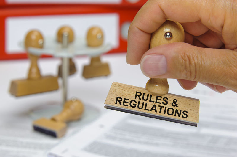 rules and regulations printed on rubber stamp in hand Authority Government Regulate Rules Statement Announcement Close-up Complaint Compliance Condition Document Guidelines Holding Human Hand Justice Policy Priorities Priority Privacy Regulations Request Rule Stamp Terms Text