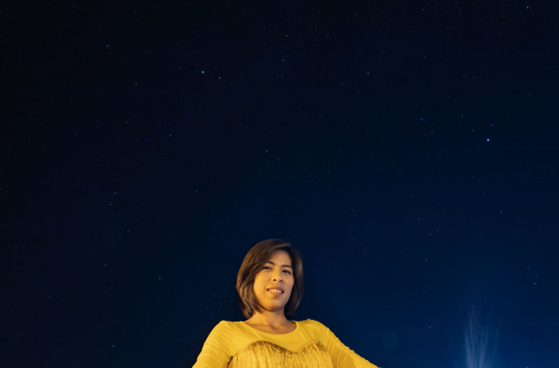 Portrait of smiling woman against blue sky at night