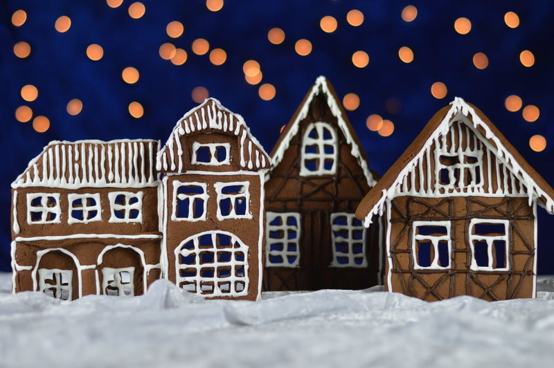 Gingerbread houses against illuminated lights at night