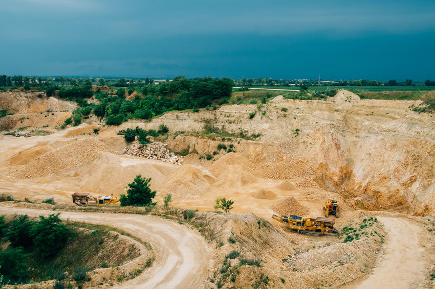 Minerals Construction Industry Day Environment Geology High Angle View Industry Land Land Vehicle Landscape Mine Mining Mode Of Transportation Non-urban Scene Outdoors Plant Quarry Road Scenics - Nature Sky Stone Surface Mine Transportation Truck Vehicle