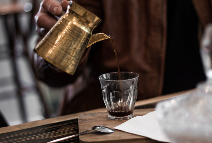 Arabic Coffee Arabic Coffee Pot Close-up Day Drink Focus On Foreground Food And Drink Freshness Holding Human Body Part Human Hand Indoors  Midsection One Person People Pouring Real People Refreshment Table Water